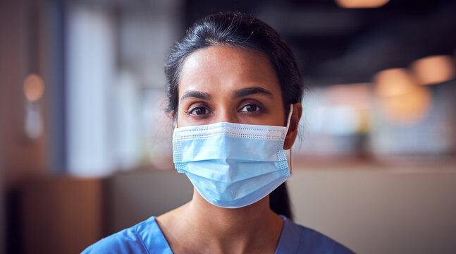 Female Doctor In Face Mask Wearing Scrubs Under Pressure In Busy Hospital During Health Pandemic