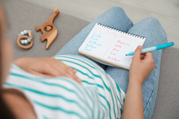 Pregnant woman with baby names list sitting on sofa, closeup