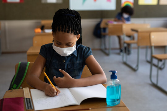 Black African American Girl wearing face mask writing while sitting on her desk at school