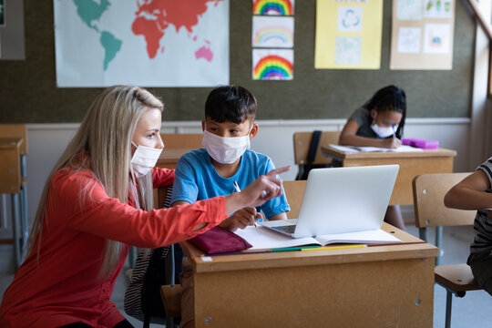 Female teacher and boy wearing face masks using laptop in class at school