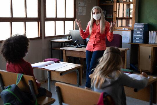 Female teacher wearing face mask teaching in class at school