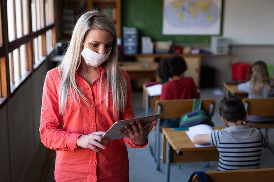 Female teacher wearing face mask using digital tablet at school