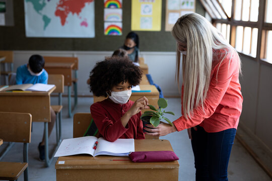 Female teacher wearing face mask showing a plant pot to a boy in school