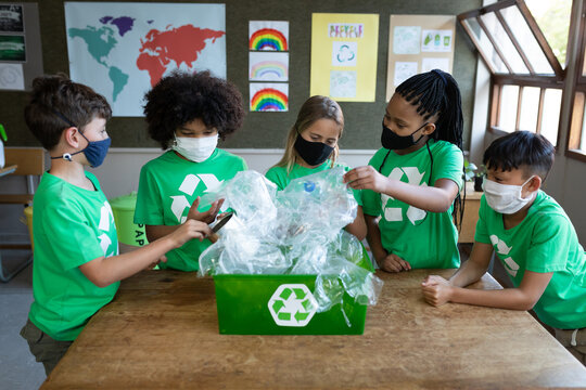 Portrait of group of kids wearing face masks touching plastics item in recycle container in class