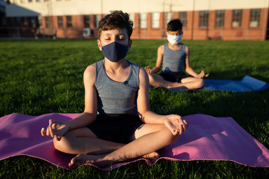 Boys wearing face masks performing yoga in school garden
