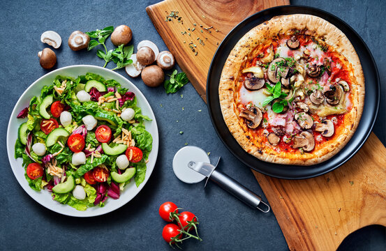pizza and salat ready to eat on a stone undergound.