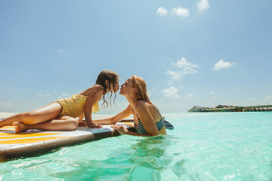Girl kissing her mother while lying on paddleboard in sea