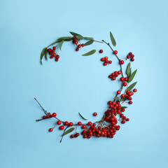 Red berries and leaves arranged in shape of wreath on light blue background, flat lay with space for text. Autumnal aesthetic
