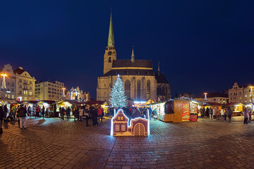 Plzen, Czech Republic. Panoramic view of Christmas market at the Republic Square close to Cathedral of St. Bartholomew in dusk.