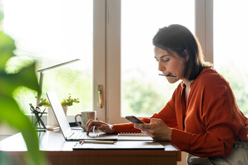 Businesswoman using mobile phone while working at home