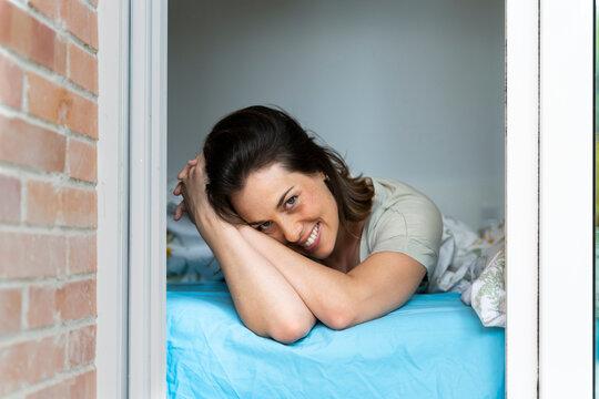 Happy woman relaxing in bedroom seen through window