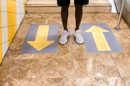 Legs of young man standing by arrow symbols on floor at subway station