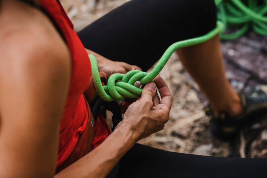 Female climber adjusting ropes while preparing for rock climbing