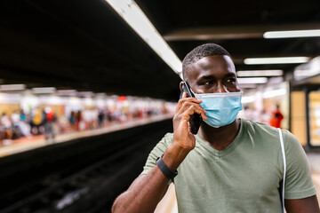 Young man wearing mask talking over smart phone while standing at subway station