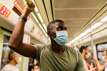 Young man wearing mask looking away while standing in subway train