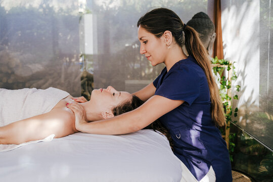 Mid adult woman massaging female customer's neck lying on table in spa