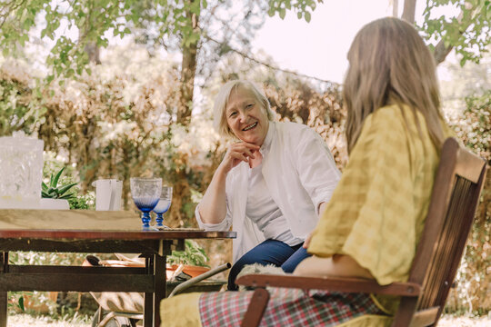 Happy senior woman talking with daughter while sitting at table in yard