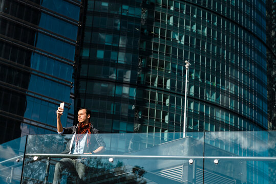 Fashionable man taking selfie with modern building in background