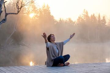 Adult woman meditating onÔøΩlakeshoreÔøΩjetty at foggy sunrise