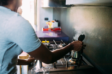 Close-up of woman making coffee on stove in kitchen