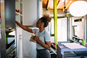 Mid adult woman searching in cabinet at home