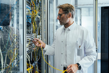 Mature man plugging transceiver on fiber optic cable into rack