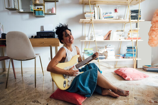 Woman playing guitar in living room