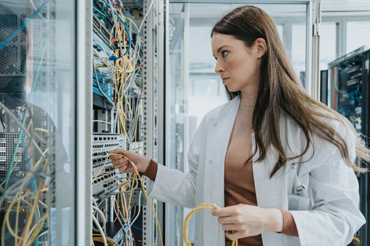 Young woman plugging transceiver on fiber optic cable in data center