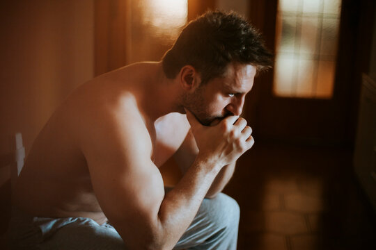 Close-up of shirtless thoughtful man sitting at home