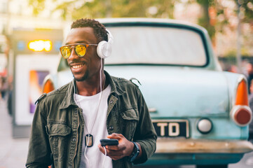 Smiling young man wearing sunglasses listening music through headphones against vintage car in city