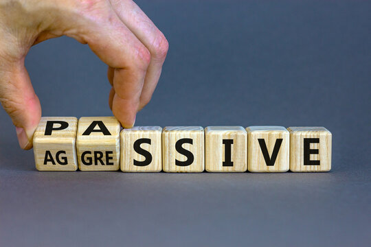 Hand turns cubes and changes the word 'passive' to 'aggressive', or vice versa. Business and psychological concept. Beautiful grey background, copy space.
