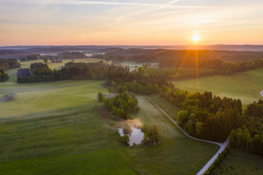 Germany, Bavaria, Upper Bavaria, Tolzer Land, near Eurasburg, Field with pond at sunrise, aerial view