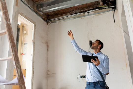 Architect using tablet in a house under construction