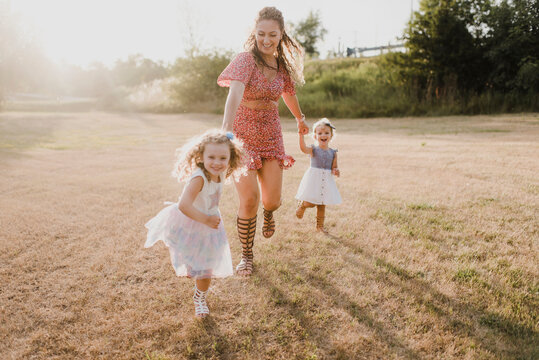 Happy mother running with daughters on a meadow in backlight