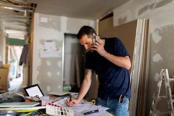 Man on the phone working on construction plan