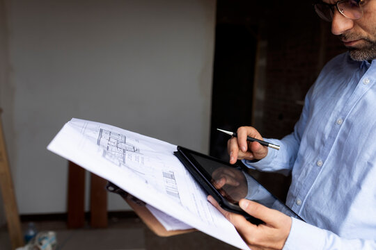 Architect at work with tablet and construction plan