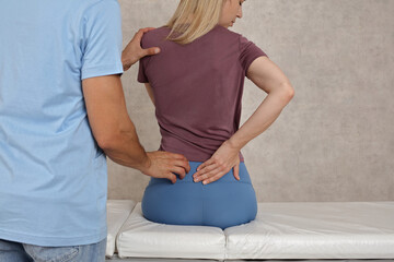 Woman suffering from low back pain during medical exam. Chiropractic, Osteopathy, Physiotherapy. Bad posture correction