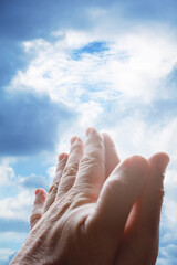 Hands praying and sky