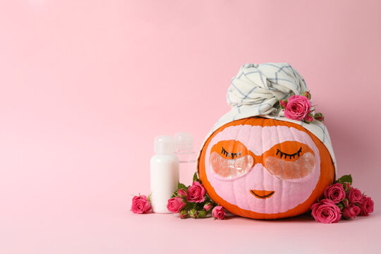 Skincare supplies, pumpkin with eye patches and towel on pink background