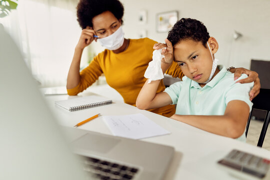 African American boy feeling stressed out while homeschooling with mother during coronavirus epidemic.