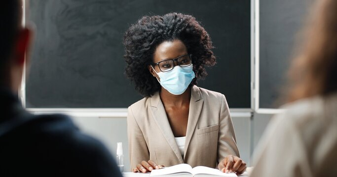 Young African American female teacher in glasses and medical mask sitting at table in school at class, reading textbook and teaching. Literature lesson. Woman educator in front of students or pupils.
