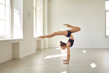 Girl keeping balance on hands and practicing rhythmic gymnastics