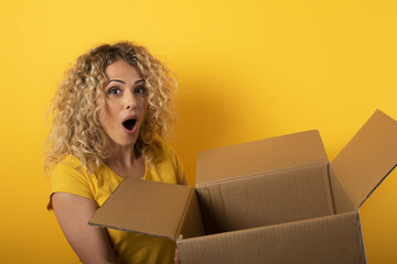 Happy woman receives a package from online shop order. Yellow background.
