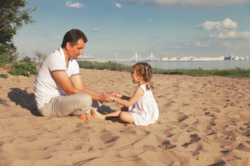 dad holds in palms hands of his little daughter in white dress are sitting on beach on sunny day