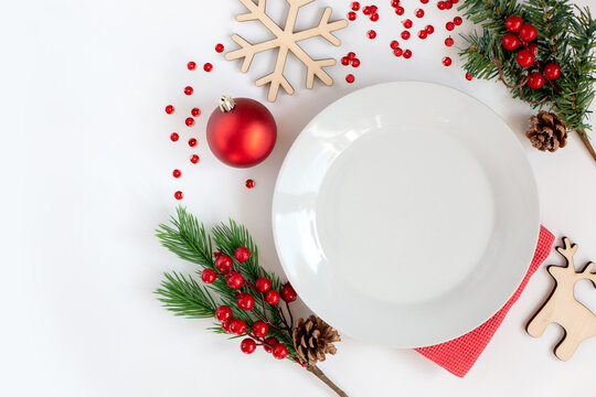 White clean round plate, on a white table with Christmas decorations
