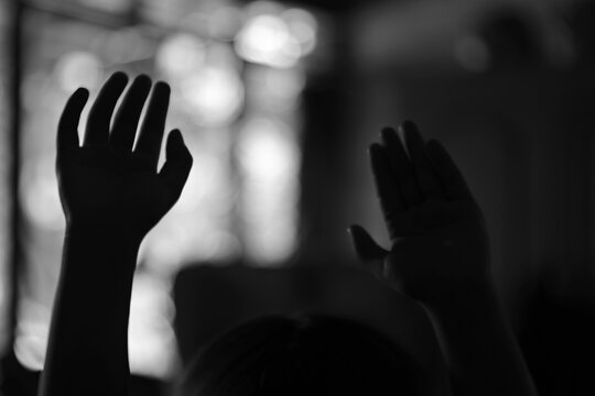 Silhouette of a person's hands raised in grayscale - worship concept