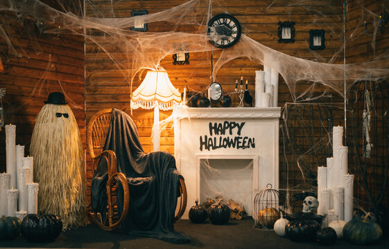 Photo of a Halloween decor with a fireplace and a rocking chair. Interior is decorated for Halloween, photozone. Background.
