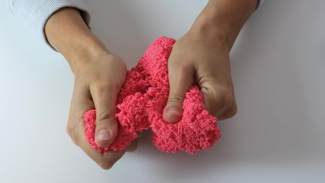 Hands crushing and crumpling pink plasticine with small balls inside, anti stress and relaxing game, close up
