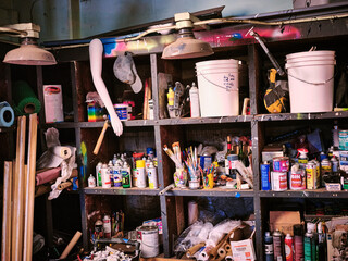 Shelves in an artists studio packed with clutter supplies and material