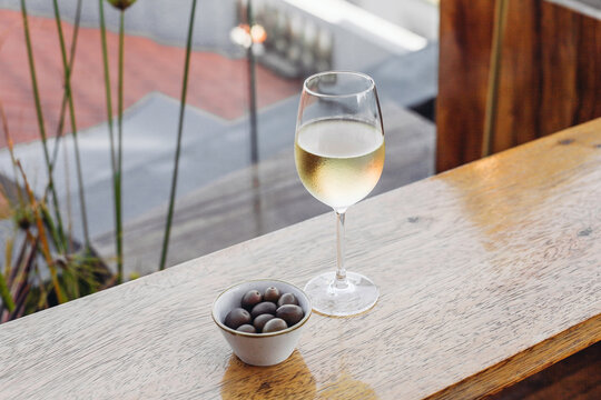 A glass of wine with olives in a bar, rooftop view